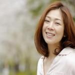 桜を背景にとる女性