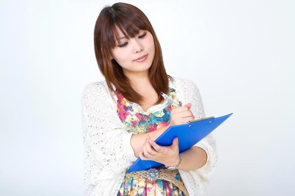 青い下敷きの上に書き物をする女性