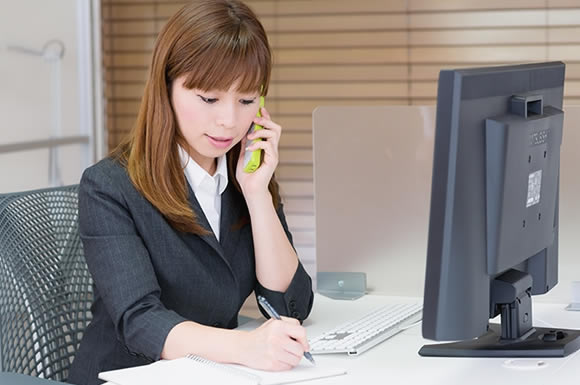電話をかけながら仕事する女性