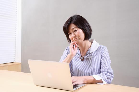 パソコンを眺める年配の女性